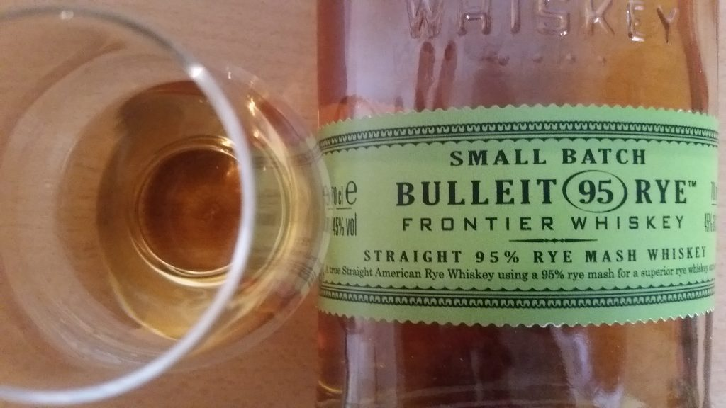 A bottle and glass of Bulleit 95 Rye