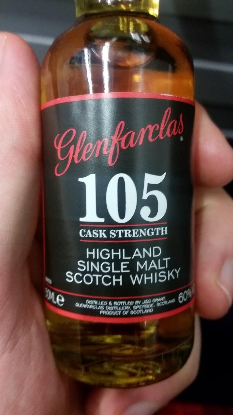 A mini bottle of Glenfarclas 105 Cask Strength in a hand
