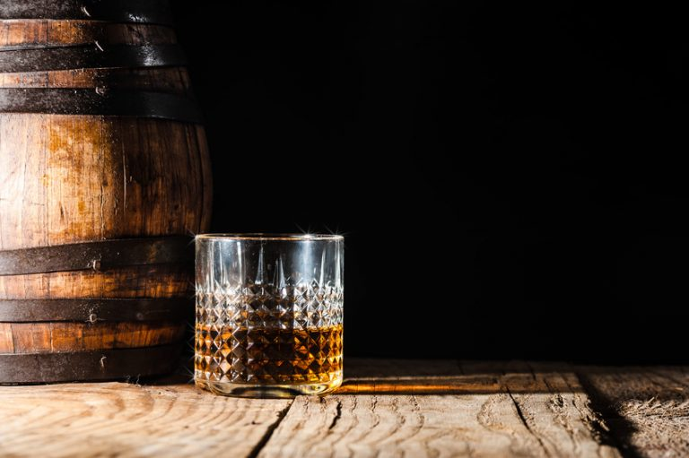 A glass of whiskey next to a barrel