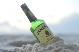 A bottle of Jamesons Irish whiskey submerged in sand