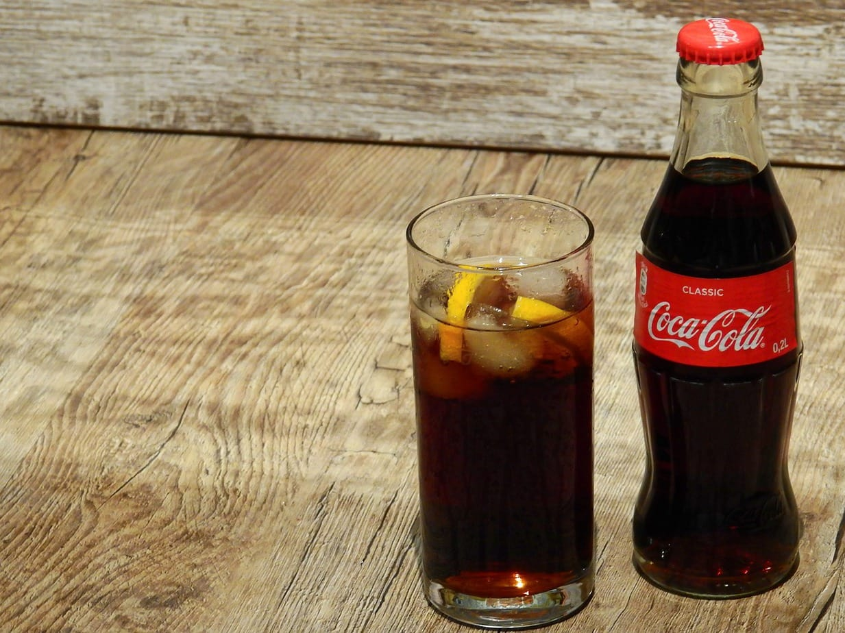 A bottle and glass of coke