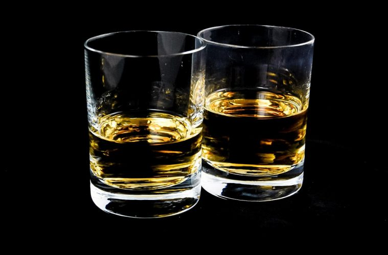Two glasses containing straight whisky
