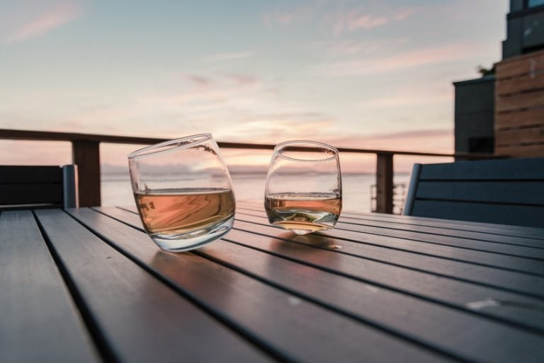 Two tilted whiskey tumblers on a table