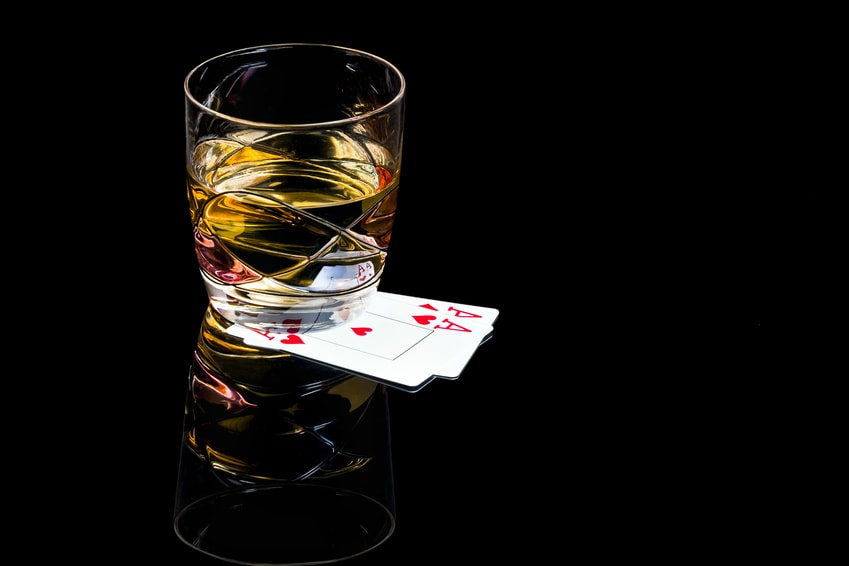 A glass of whiskey with the ace of hearts and diamonds