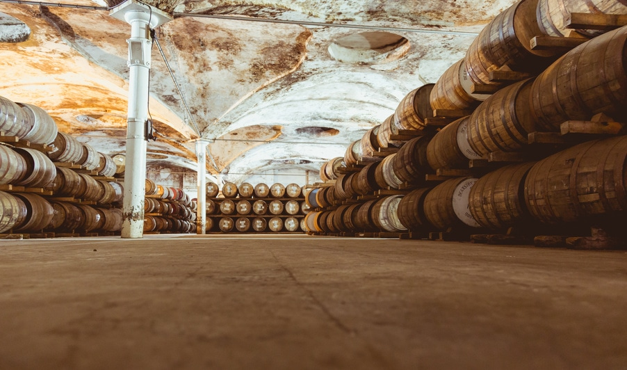 Many bourbon barrels in a warehouse