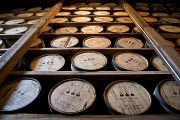 Whiskey barrels on shelves at a distillery