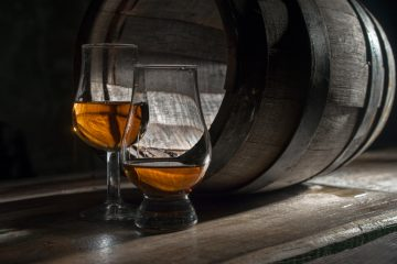 Whiskey in 2 different glasses next to a barrel