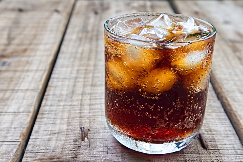 A glass of bourbon and coke with ice