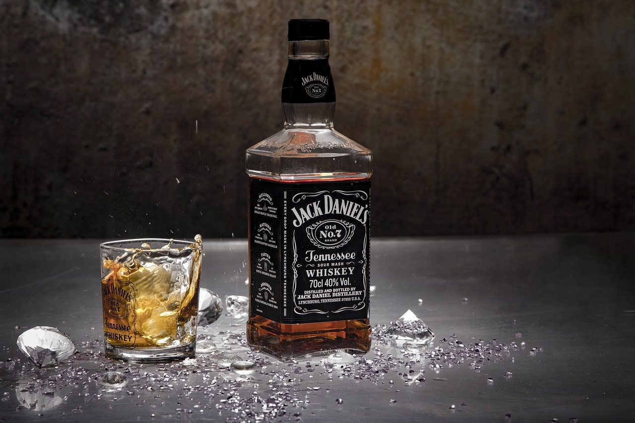 A bottle and glass of Jack Daniels with a mixer