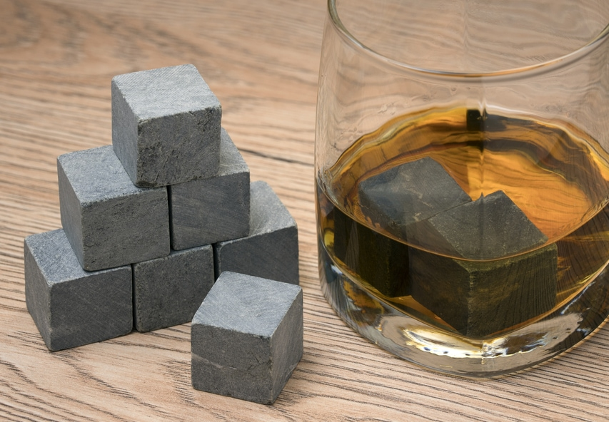 Stones in glass of whiskey on wooden background.