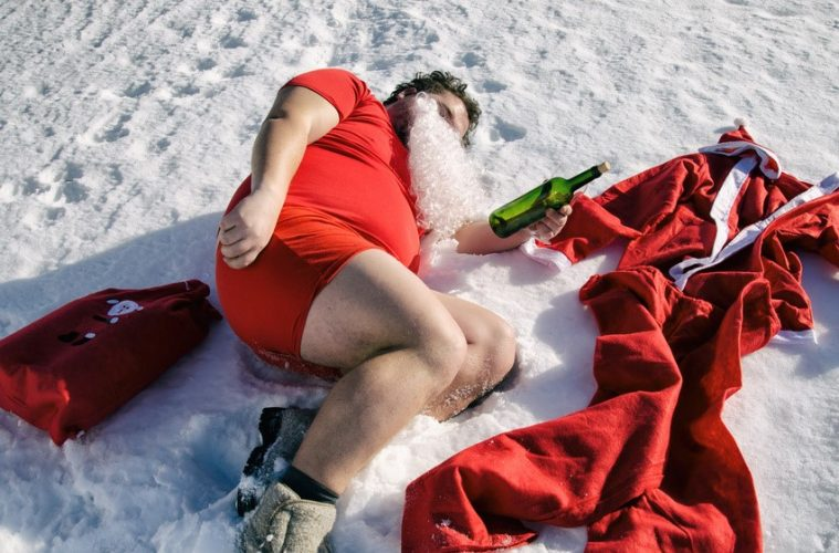 A drunk Santa lying in the snow with a bottle of whisky