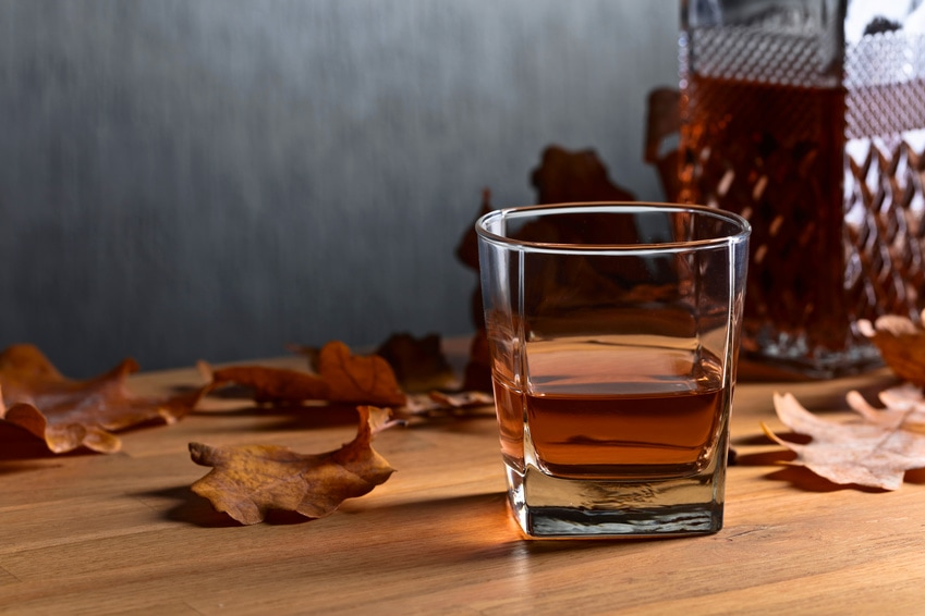 A glass of whiskey and decanter with leaves