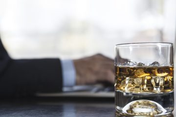 A man working on laptop with a glass of whisky near him