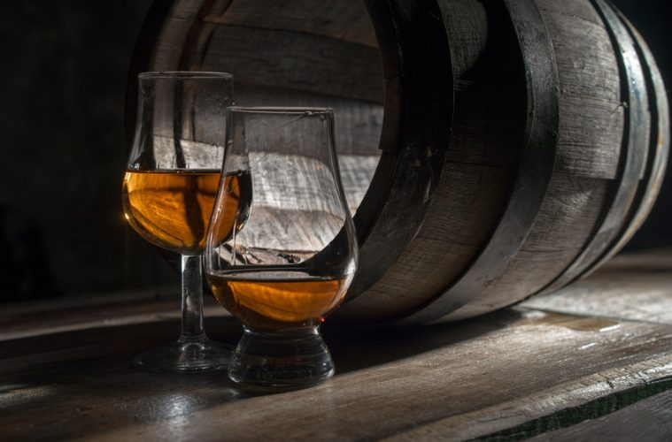 Two different whiskey glasses in front of a barrel