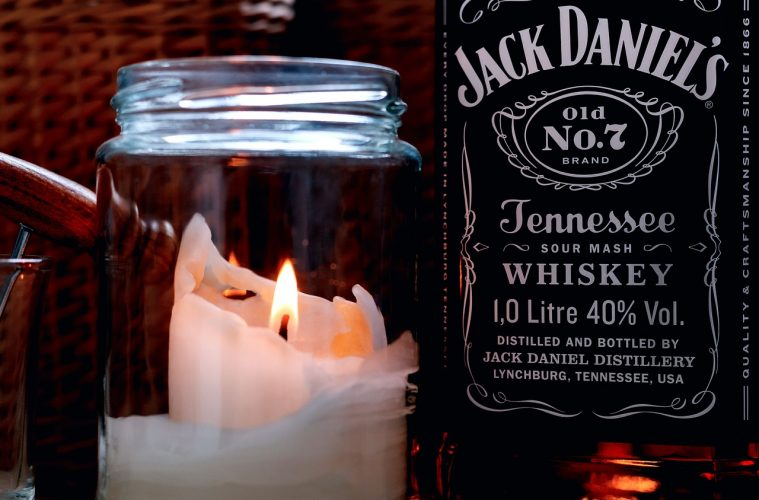A bottle of Jack Daniels Sour Mash whiskey next to a candle