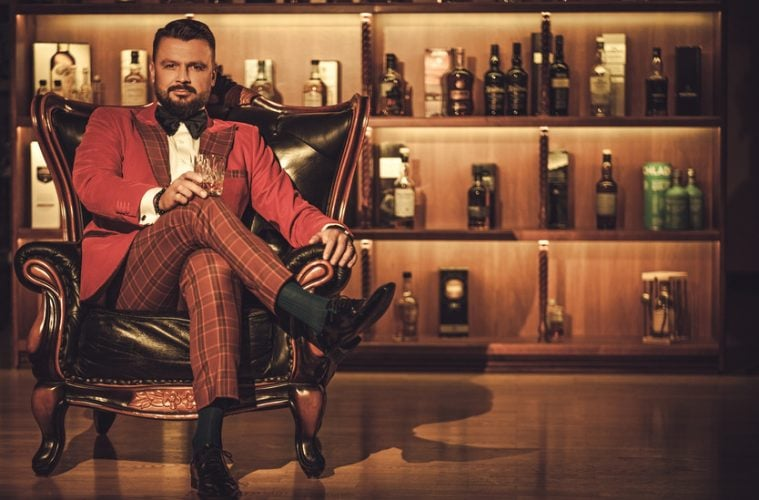 A well dressed whiskey investor sat with his collection