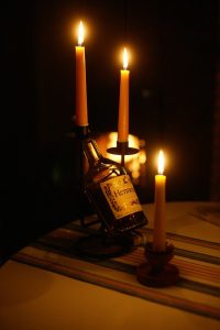 A bottle of Hennessy next to candles