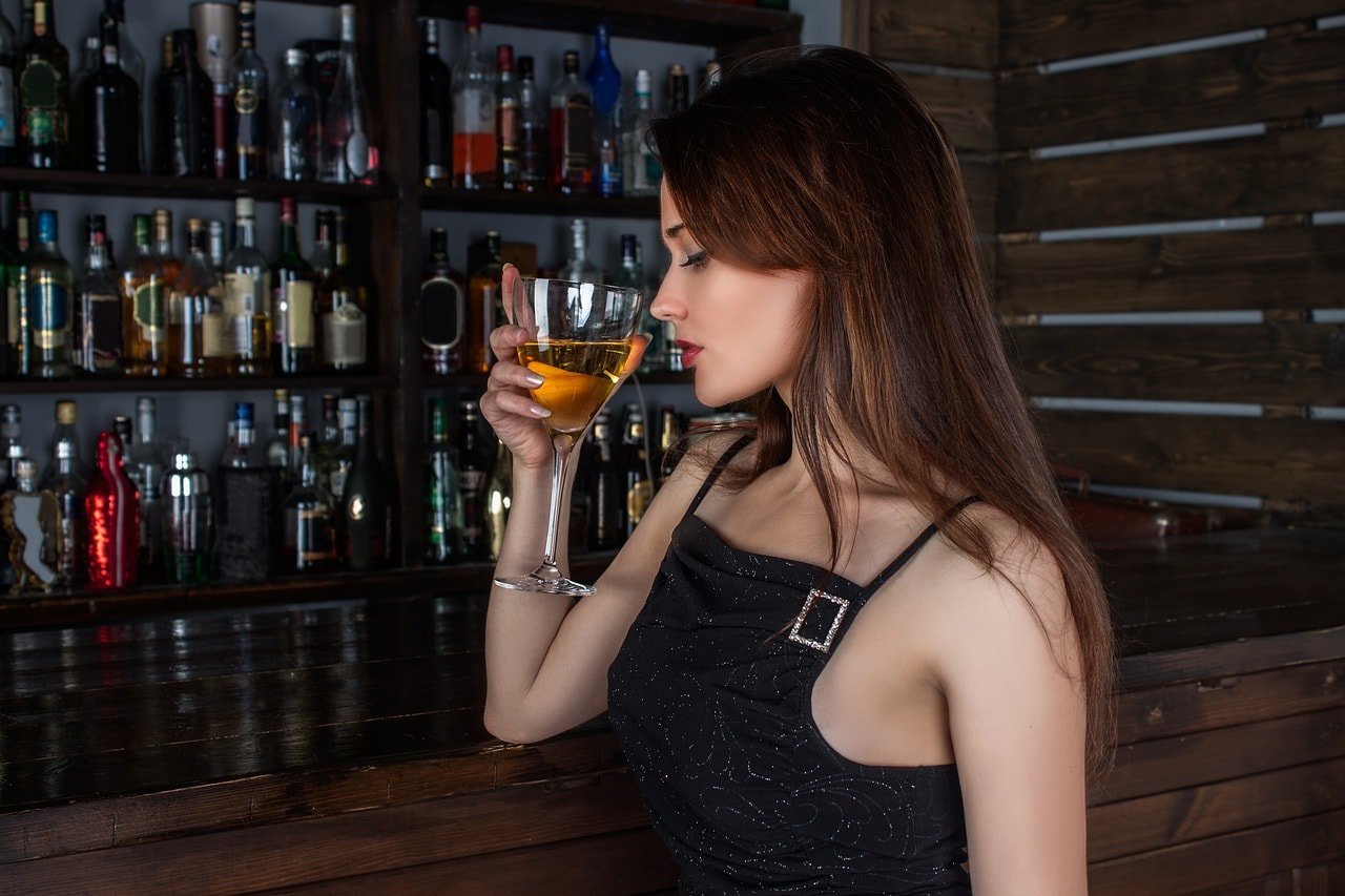 A girl drinking a whiskey cocktail
