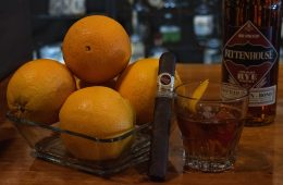 A bottle of whiskey next to a bowl of oranges