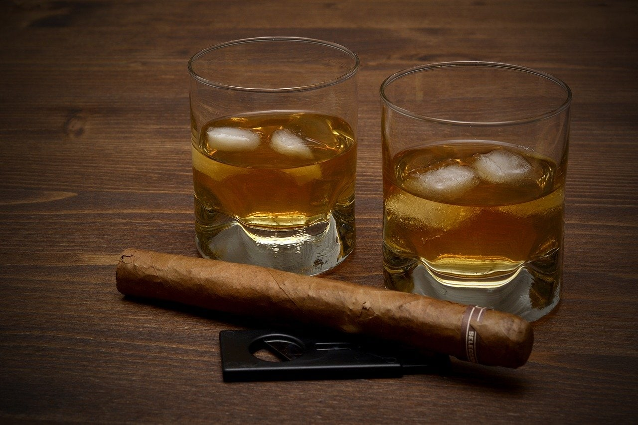 Two glasses of whiskey next to a cigar