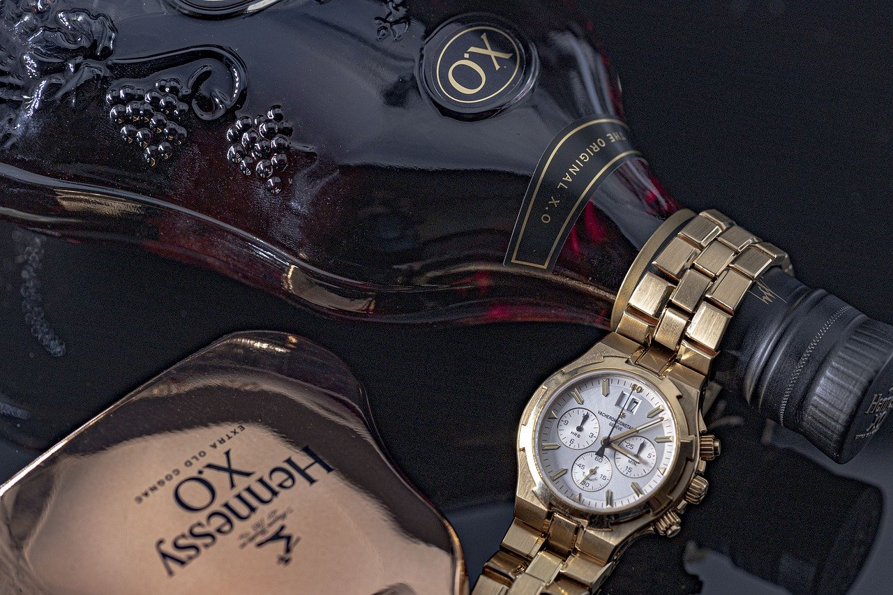 A bottle of Hennessy Cognac with a watch