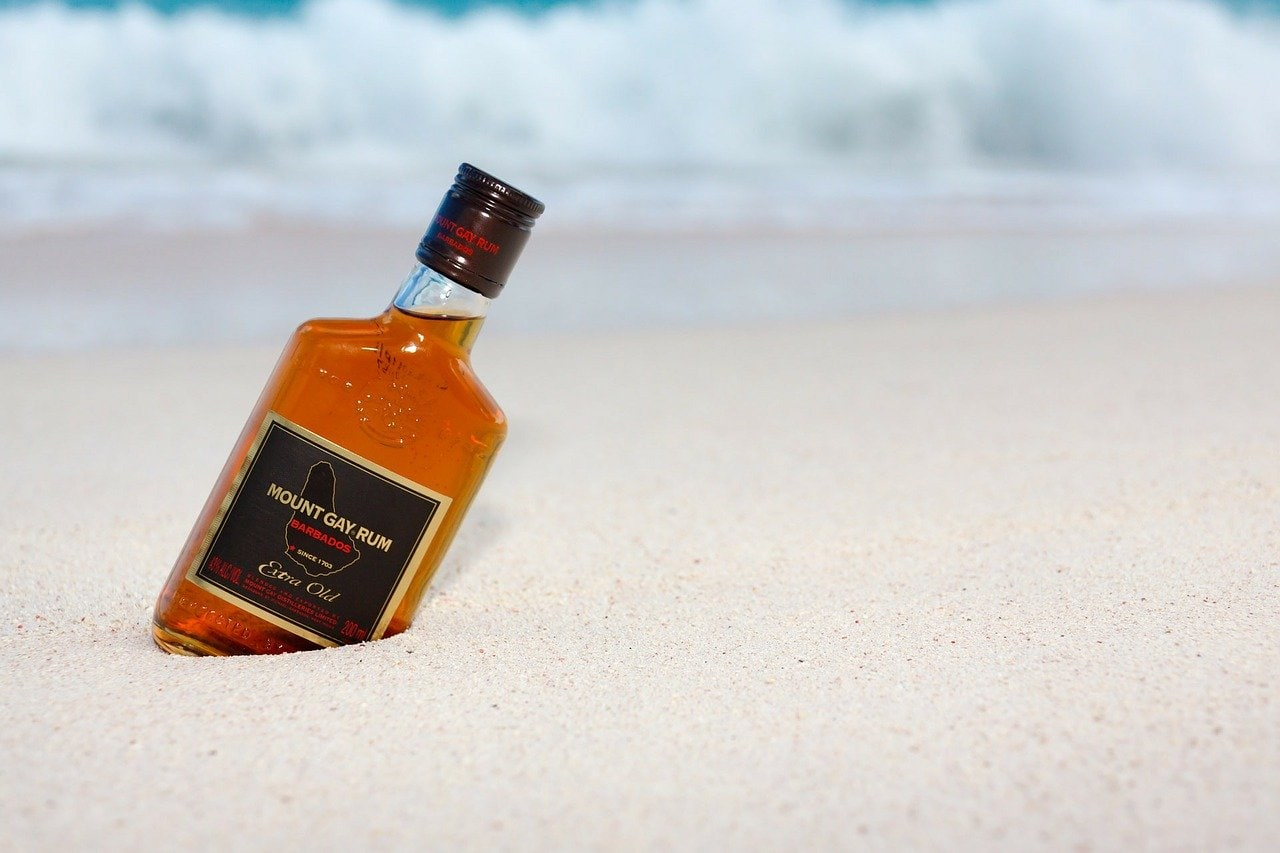 A bottle of mount Gay rum on the beach