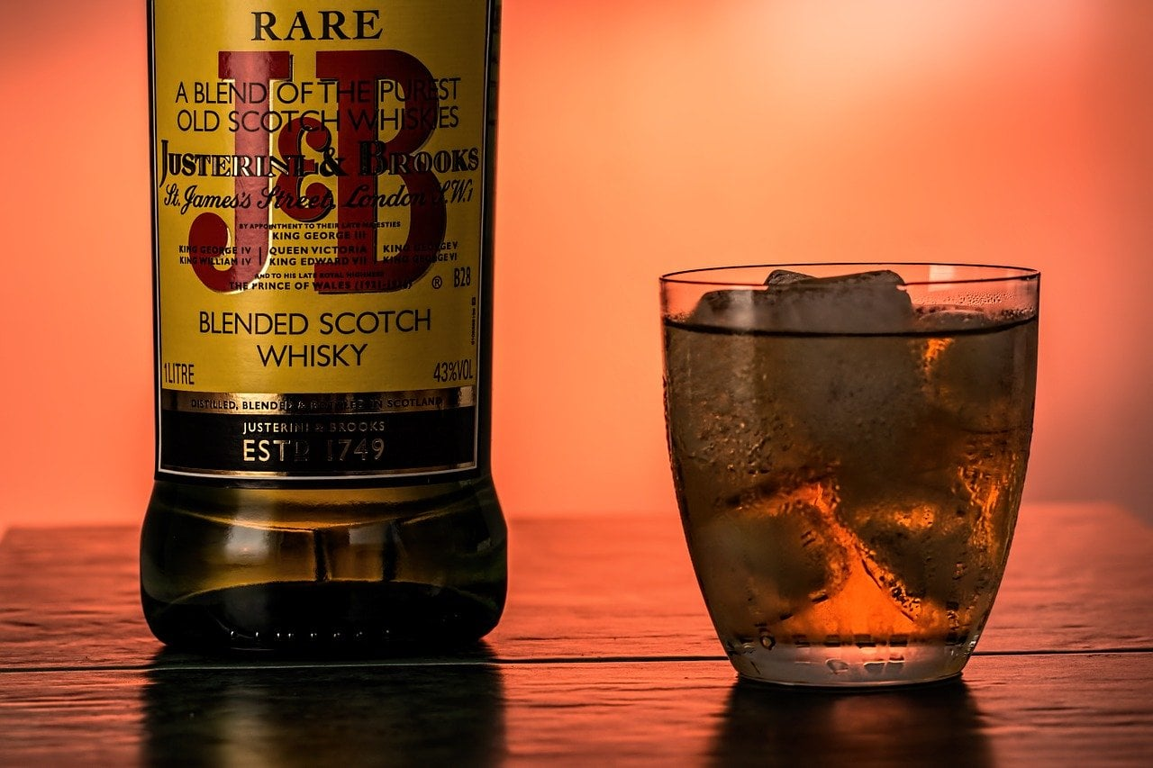 A bottle and glass of J&B Blended Scotch Whisky