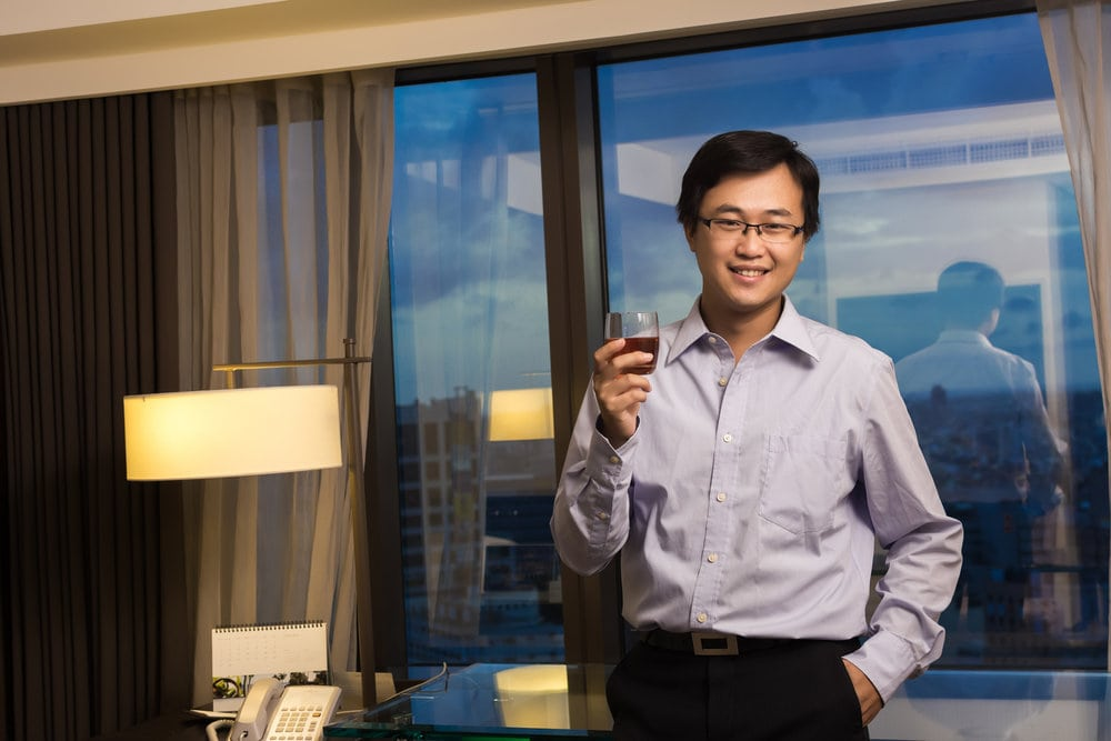 An Asian man holding a glass of whisky