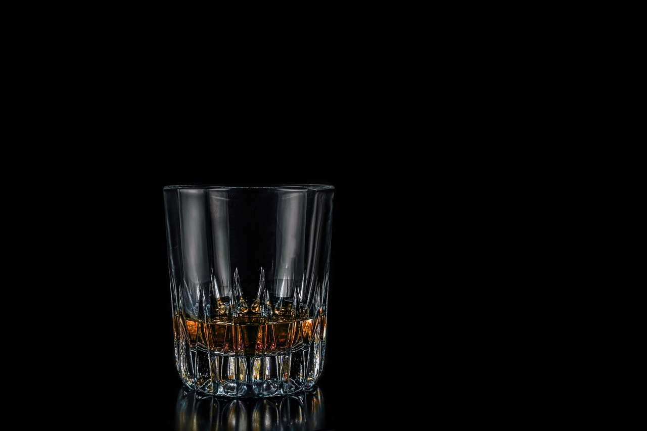 A glass of whisky with a black background