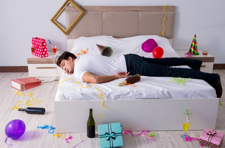 A man lying on the bed with a hangover