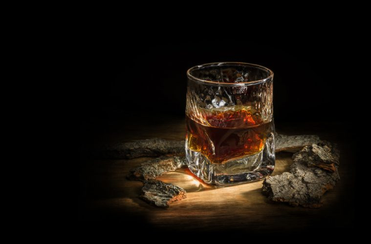 A glass of bourbon next to a piece of wood
