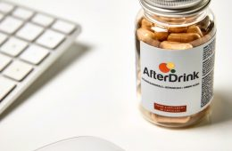 A bottle of AfterDrink next to a PC
