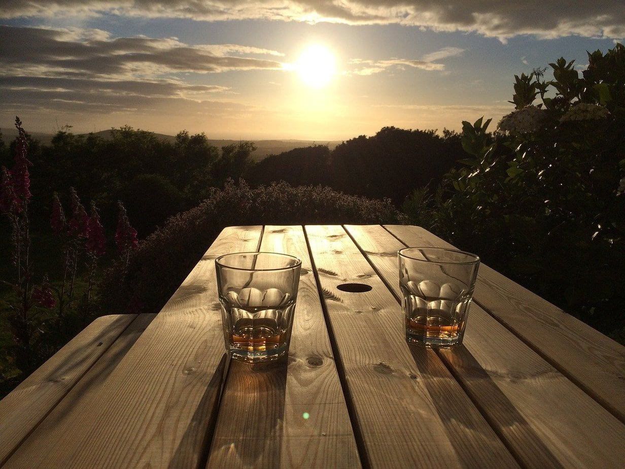 Two glasses of bourbon on a table in the sunset
