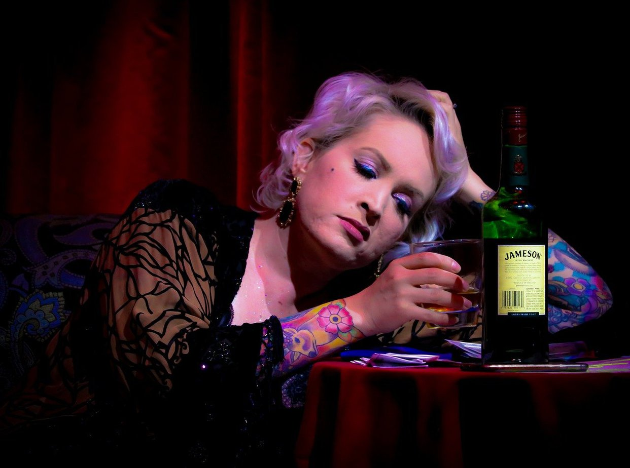 A woman drinking whiskey